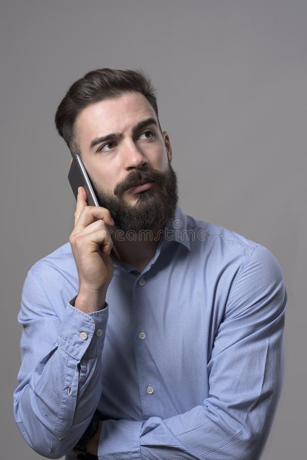 Retrato do homem de negócios farpado seguro sério que fala no telefone celular que olha acima foto de stock royalty free