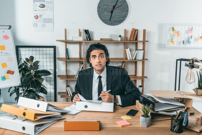 retrato do homem de negócios forçado com papéis nas mãos que olham a câmera imagem de stock royalty free
