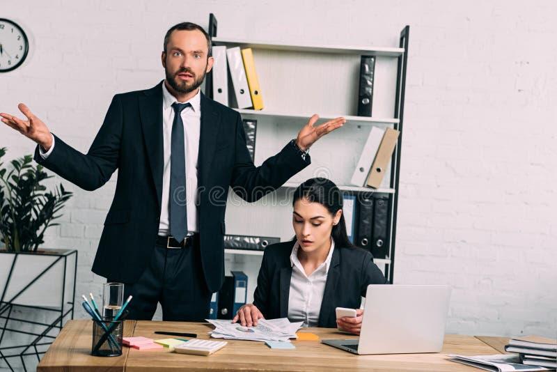 retrato do homem de negócios forçado e do colega focalizado que trabalham no local de trabalho com portátil foto de stock