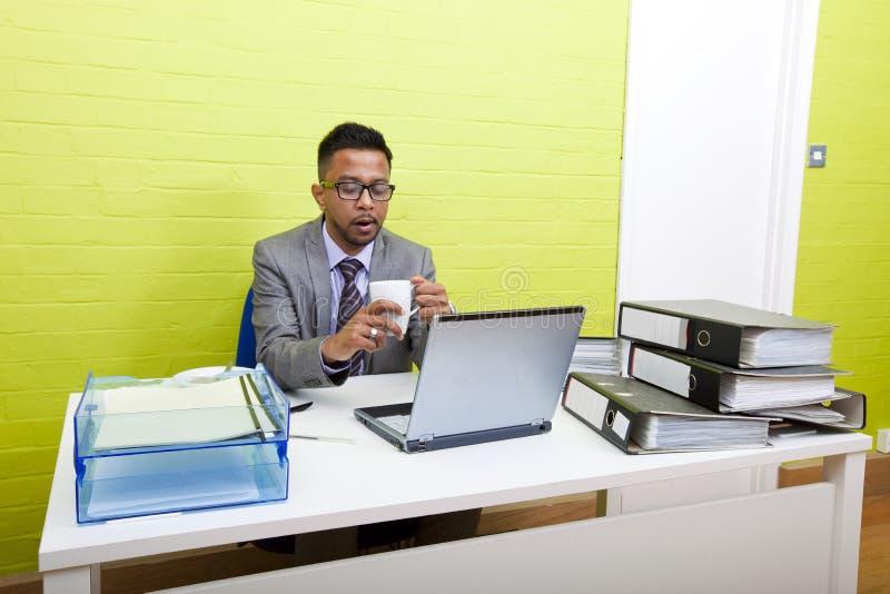 Retrato do homem de negócios indiano que guardara a caneca e que trabalha em seu computador portátil em sua mesa imagens de stock