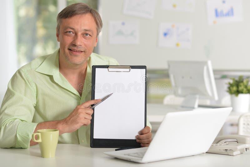 Retrato do homem de negócios maduro que trabalha na tabela com portátil em casa fotografia de stock