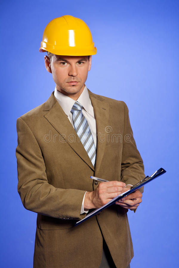 Retrato do homem de negócios na escrita amarela do capacete de segurança na prancheta fotografia de stock royalty free