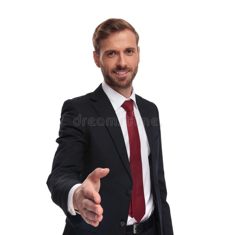 Retrato do homem de negócios novo atrativo que dá uma agitação da mão fotografia de stock royalty free