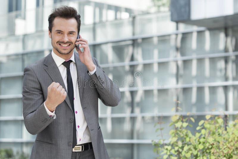 Retrato do homem de negócios novo bem sucedido que usa o telefone celular contra o prédio de escritórios fotografia de stock