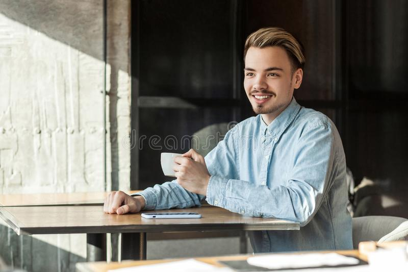 Retrato do homem de negócios novo feliz considerável no café bebendo de assento da camisa azul da sarja de Nimes, e da vista afas fotografia de stock