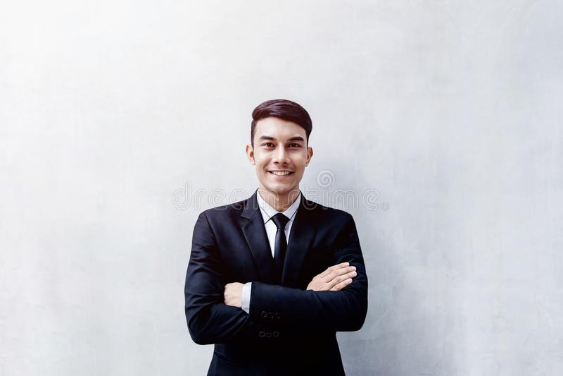 Retrato do homem de negócios novo feliz que está na parede, Smilin imagens de stock