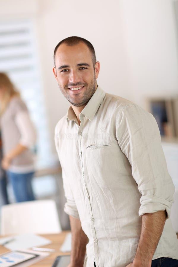 Retrato do homem de negócios novo na posição do escritório imagens de stock royalty free