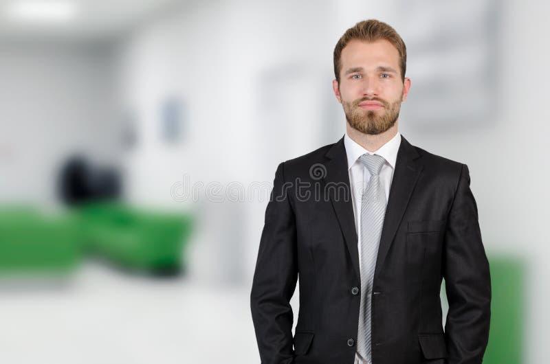 Retrato do homem de negócios novo que está no escritório imagens de stock