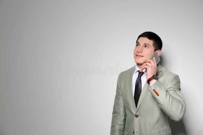 Retrato do homem de negócios novo que fala no telefone contra o fundo claro fotos de stock royalty free