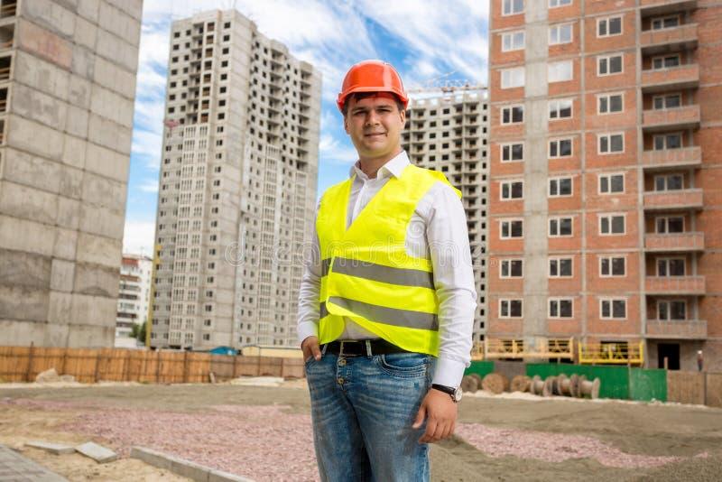 Retrato do homem de negócios novo de sorriso na veste e no capacete de segurança que estão no terreno de construção foto de stock