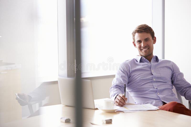 Retrato do homem de negócios ocasionalmente vestido Sitting At Desk imagens de stock