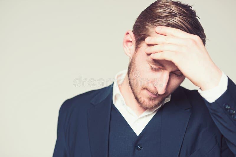Retrato do homem de negócios de pensamento com mão em sua cabeça Indivíduo farpado na camisa branca e no terno azul que sofrem de foto de stock royalty free