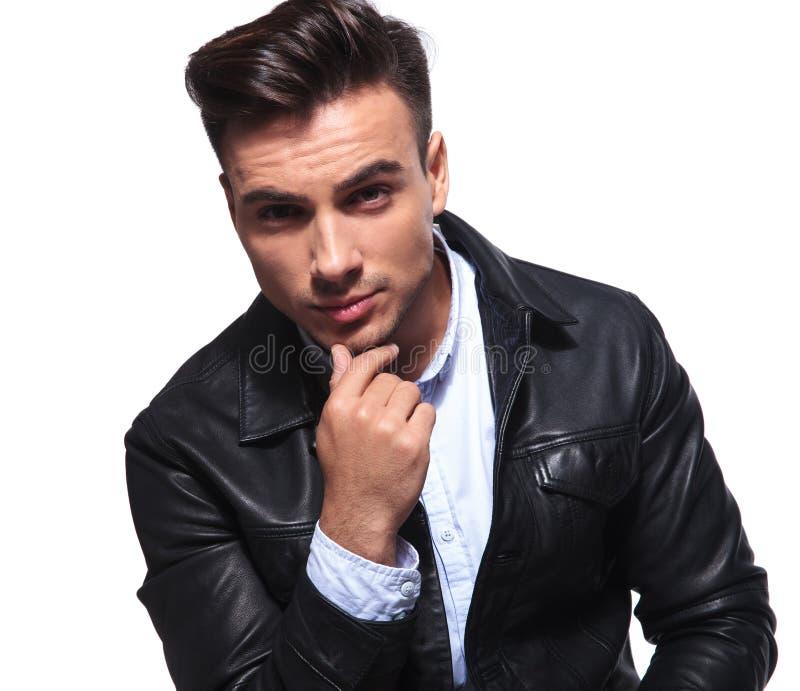 Retrato do homem de negócios pensativo novo no assento do casaco de cabedal fotos de stock