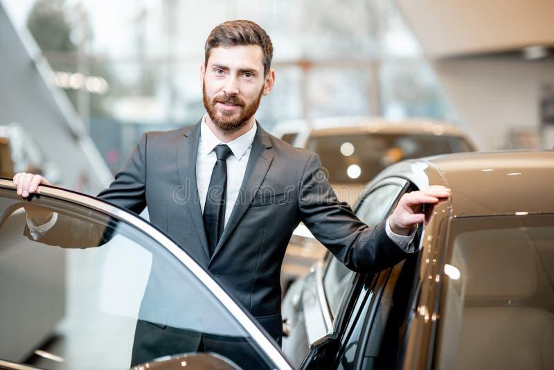 Retrato do homem de negócios perto do carro na sala de exposições foto de stock