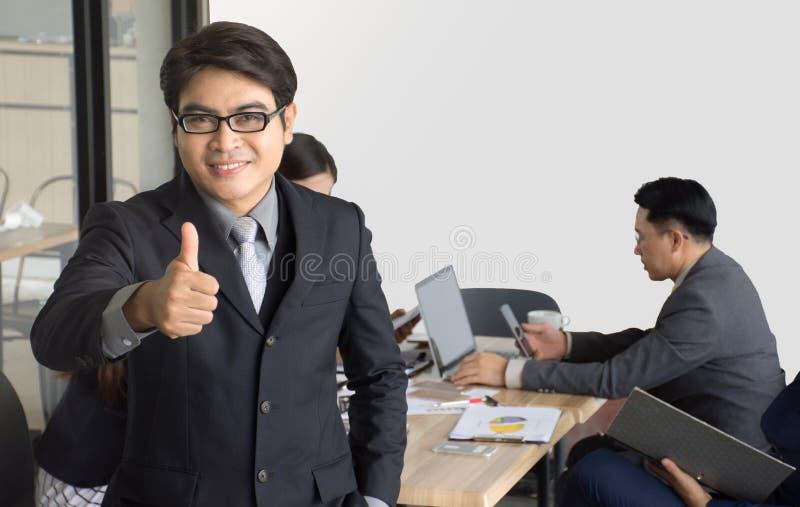 Retrato do homem de negócios que está na frente de sua equipe no escritório, homem de negócios asiático que conduz sua equipe imagem de stock royalty free