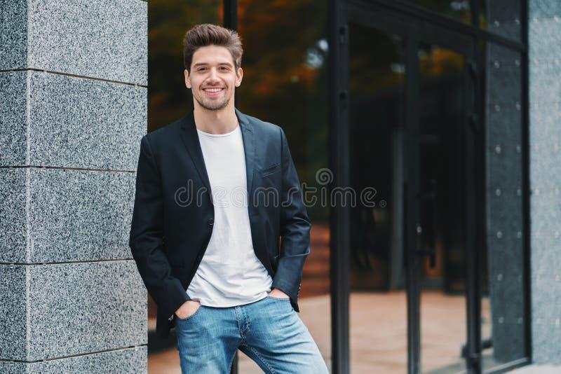 Retrato do homem de negócios seguro bem sucedido novo na cidade no fundo do prédio de escritórios Homem no terno de negócio imagem de stock royalty free