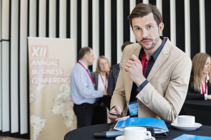 Retrato do homem de negócios seguro que guarda o telefone esperto durante a ruptura de café no centro de convenções imagens de stock royalty free