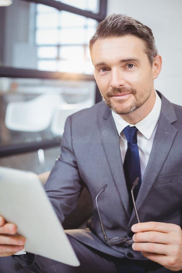 Retrato do homem de negócios seguro que guarda a tabuleta digital ao sentar-se no sofá imagem de stock