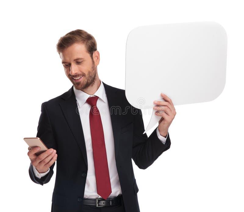 Retrato do homem de negócios de sorriso que texting ao guardar o bub do discurso fotos de stock