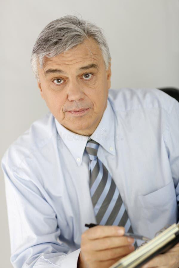 Retrato do homem de negócios superior que escuta o cliente imagem de stock