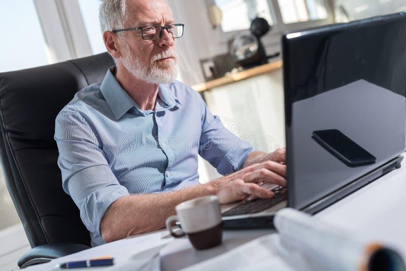 Retrato do homem de negócios superior que trabalha no portátil, luz dura imagem de stock
