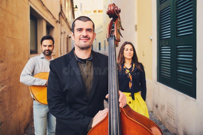 Retrato do homem de sorriso considerável em uma rua velha No fundo de dois músicos com uma guitarra e um cantor Um homem com um b foto de stock