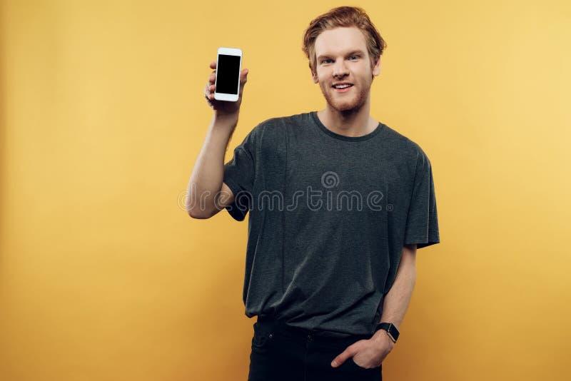 Retrato do homem de sorriso que guarda o smartphone fotografia de stock