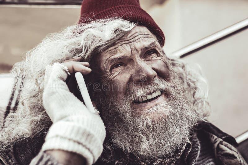 Retrato do homem desabrigado que fala no smartphone e que olha o céu fotografia de stock