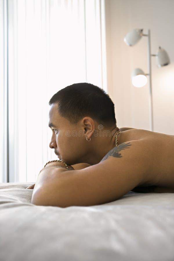 Retrato do homem descamisado que encontra-se na cama. foto de stock royalty free