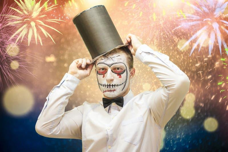 Retrato do homem do Dia das Bruxas com máscara protetora assustador no chapéu negro no fundo colorido festivo com bokeh e fogos-d imagens de stock
