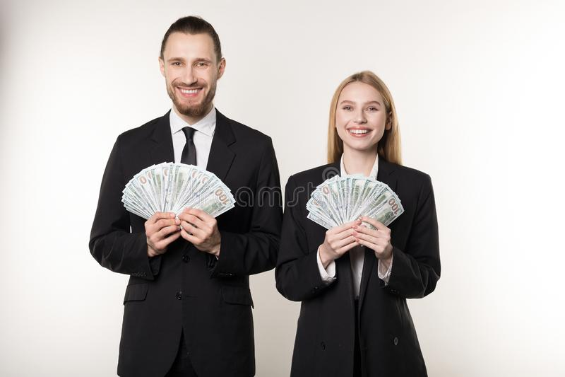 Retrato do homem e da mulher no fã preto da terra arrendada do terno do dinheiro do dólar que sorri e que olha a câmera fotografia de stock