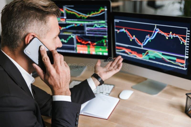Retrato do homem eficiente que fala no telefone celular ao trabalhar com os gráficos digitais no computador no escritório imagem de stock