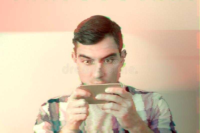 Retrato do homem entusiástico com o telefone do jogo com efeito do pulso aleatório imagens de stock royalty free