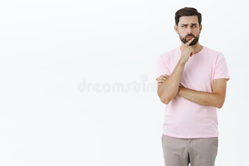 Retrato do homem farpado adulto considerável criativo no t-shirt cor-de-rosa que faz hmm o dedo da terra arrendada do som nos bor imagem de stock royalty free