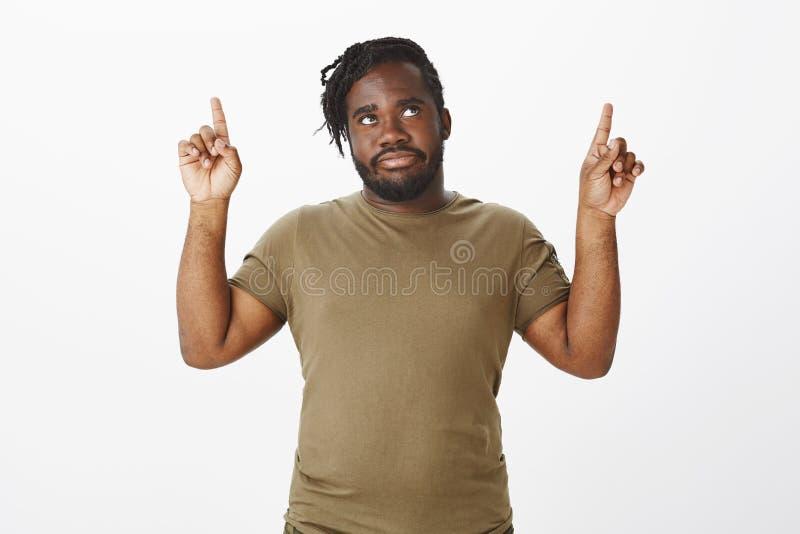 Retrato do homem farpado africano desagradado incomodado na roupa militar, aumentando os indicadores, olhando e apontando acima fotos de stock