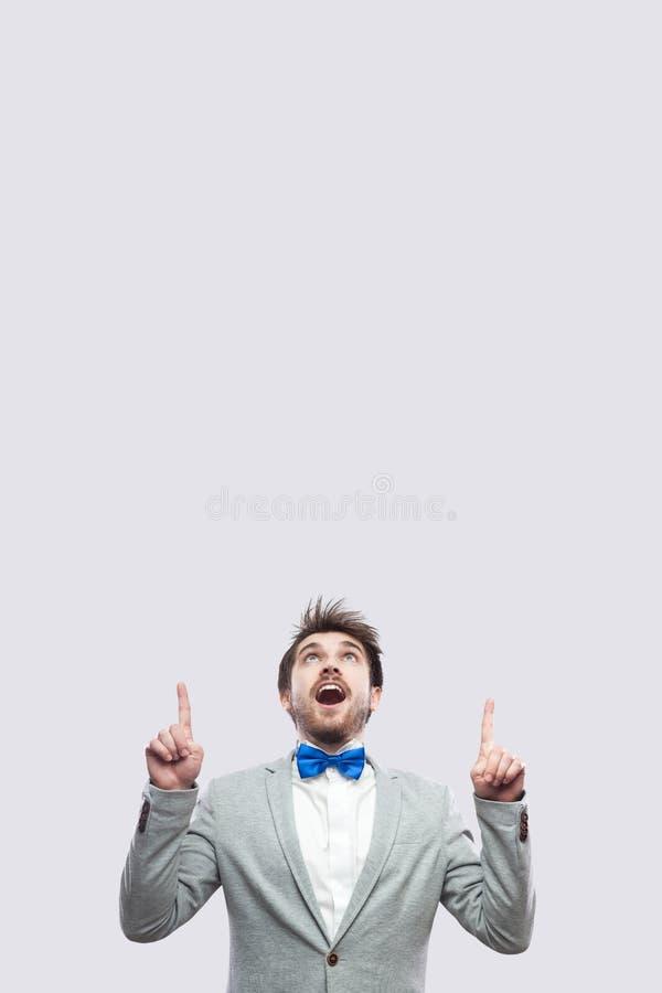 Retrato do homem farpado considerável surpreendido no terno cinzento ocasional e na posição azul do laço que olham e que apontam  foto de stock royalty free