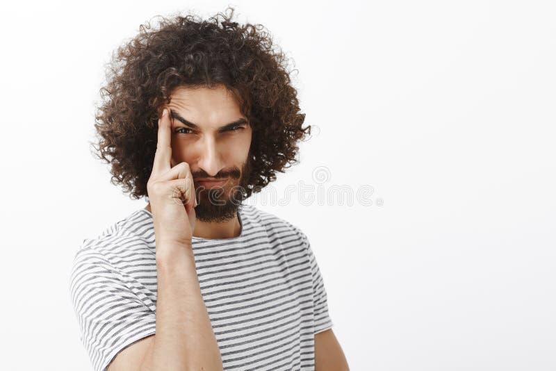 Retrato do homem farpado maduro brincalhão suspeito com cabelo encaracolado, a sobrancelha de levantamento com indicador e olhar  foto de stock royalty free
