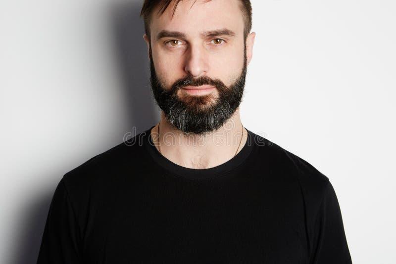 Retrato do homem farpado no tshirt preto no fundo vazio fotos de stock
