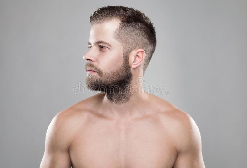 Retrato do homem farpado novo com um corte novo do cabelo imagens de stock