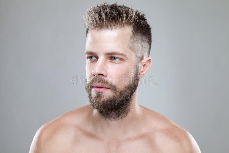 Retrato do homem farpado novo com um corte novo do cabelo foto de stock