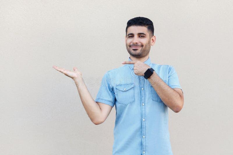 Retrato do homem farpado novo considerável satisfeito feliz na camisa azul que está, guardando, apontando algo e olhando a câmera fotografia de stock royalty free