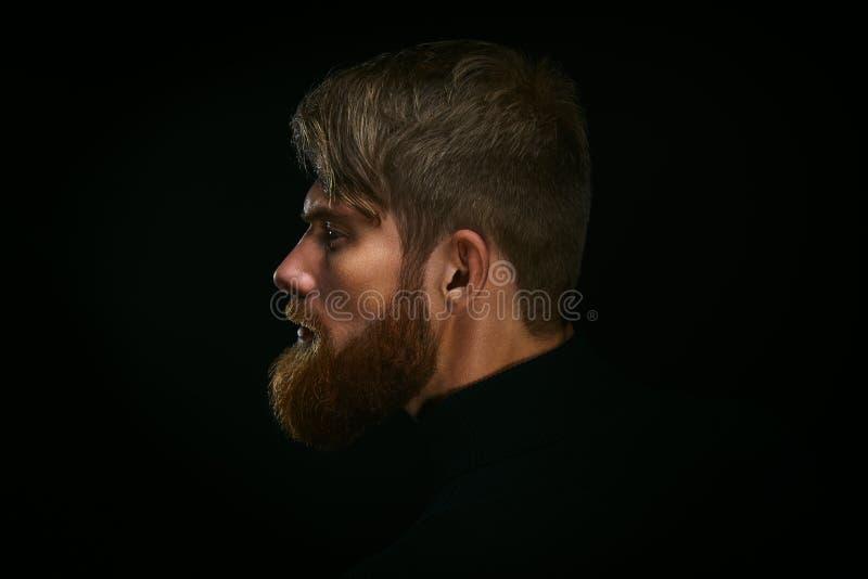 Retrato do homem farpado novo no indivíduo preto w do fundo fotos de stock royalty free