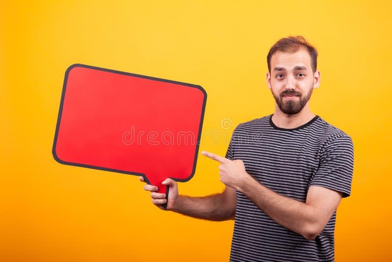Retrato do homem farpado novo que aponta em sua placa de informação sobre o fundo amarelo fotografia de stock