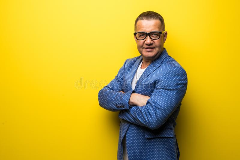 Retrato do homem feliz da Idade Média do divertimento no terno e dos eyesglasses isolados no fundo amarelo imagem de stock royalty free