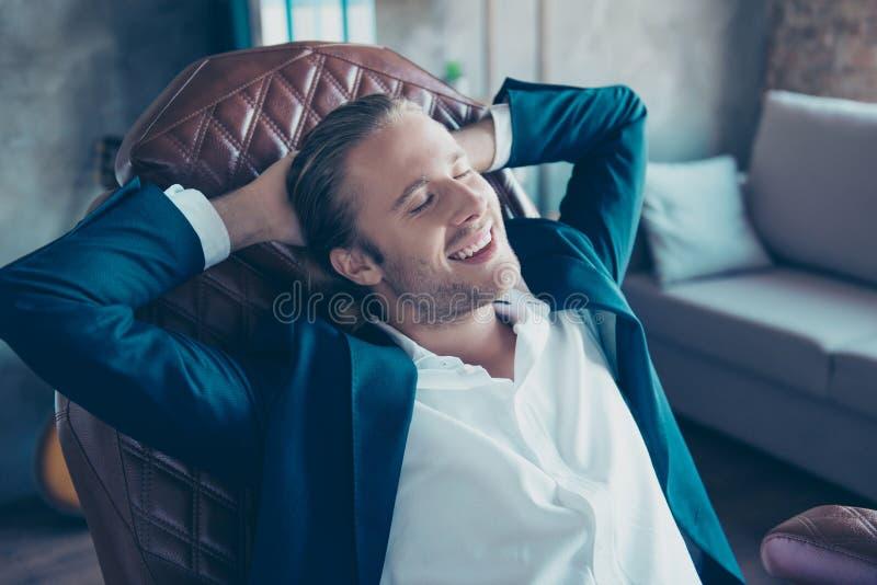 Retrato do homem feliz de sorriso atrativo que senta-se em sua mesa dentro foto de stock