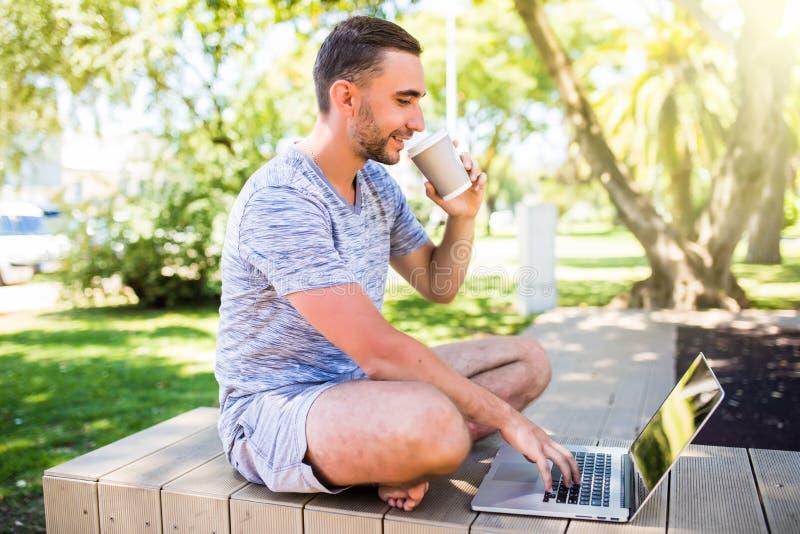 Retrato do homem feliz novo com portátil e xícara de café no banco no parque imagem de stock