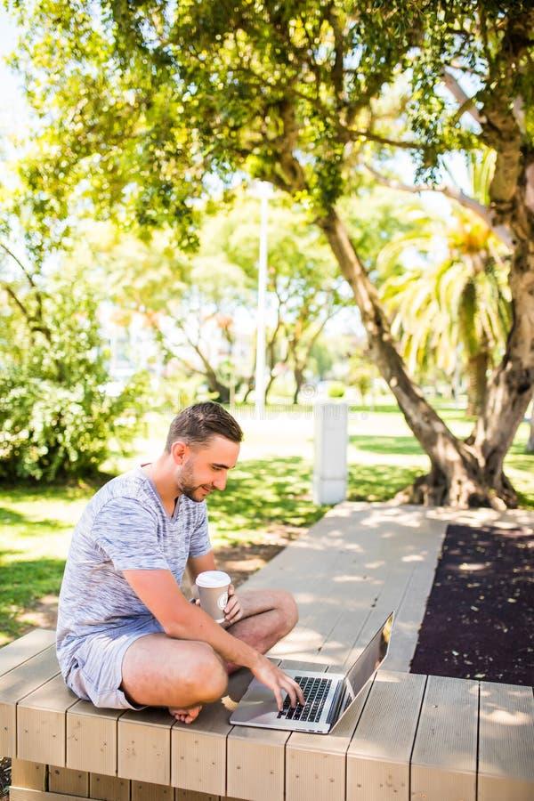 Retrato do homem feliz novo com portátil e xícara de café no banco no parque fotos de stock
