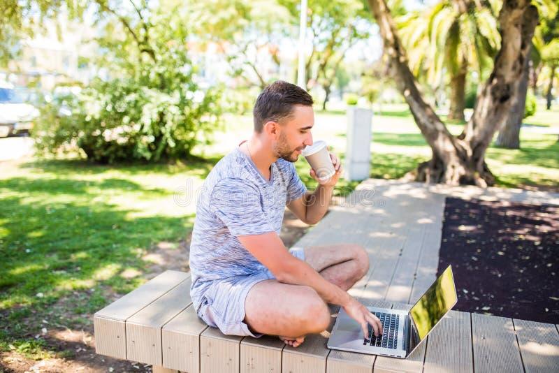 Retrato do homem feliz novo com portátil e xícara de café no banco no parque fotos de stock royalty free
