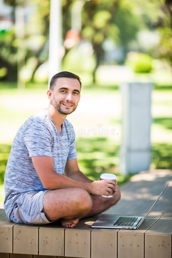 Retrato do homem feliz novo com portátil e xícara de café no banco no parque imagens de stock royalty free