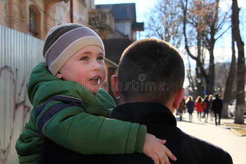 Retrato do homem feliz que guarda seu filho no pescoço no fundo do céu foto de stock royalty free